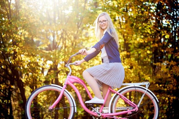 Attraktive reisende frau, die auf modernem rosa dame fahrrad auf beleuchtet durch herbstsonnenpark auf hellem buntem goldenen bokeh-baumhintergrund reitet.