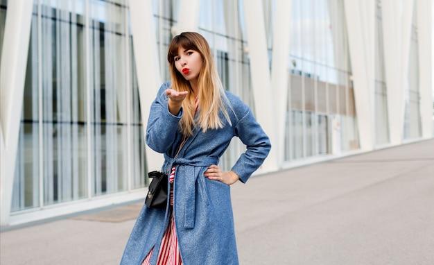Attraktive reizende frau im blauen mantel, der auf modernen gebäuden aufwirft