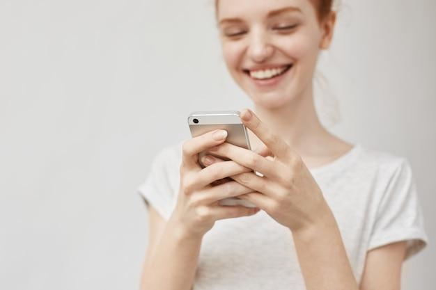 Attraktive rothaarige frau, die ar telefon lächelnd sucht.