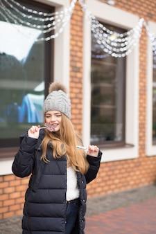 Attraktive rothaarige junge frau, die graue strickmütze trägt und weihnachtsbonbons beißt