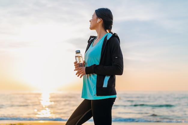 Attraktive schlanke frau, die sportübungen am morgensonnenaufgangstrand in der sportkleidung, durstiges trinkwasser in der flasche, gesunder lebensstil tut, musik auf drahtlosen kopfhörern hörend, glücklich lächelnd macht