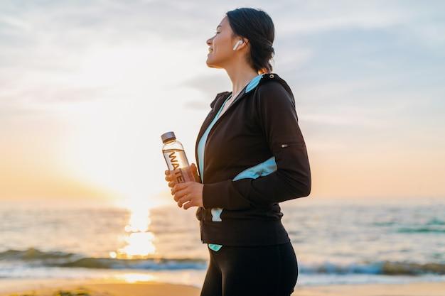 Attraktive schlanke frau, die sportübungen am morgensonnenaufgangstrand in der sportkleidung tut, wasser in der flasche hält, gesunden lebensstil, musik auf drahtlosen kopfhörern hörend