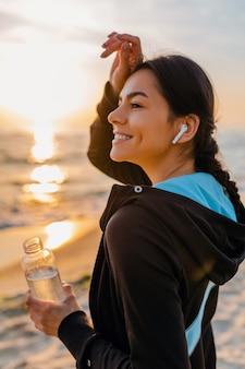 Attraktive schlanke frau, die sportübungen am morgensonnenaufgangstrand in sportbekleidung, durstiges trinkwasser in der flasche, gesunder lebensstil, musik hören auf drahtlosen kopfhörern, heißer sommertag tut