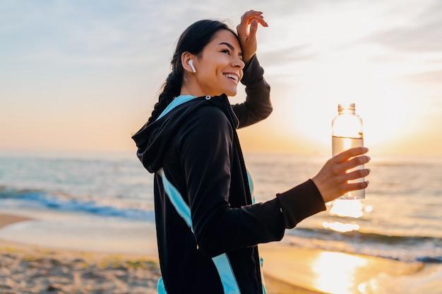 Attraktive schlanke frau, die sportübungen am morgensonnenaufgangstrand in sportkleidung, durstiges trinkwasser in der flasche, gesunder lebensstil, musik auf drahtlosen kopfhörern hörend macht, sich heiß fühlt