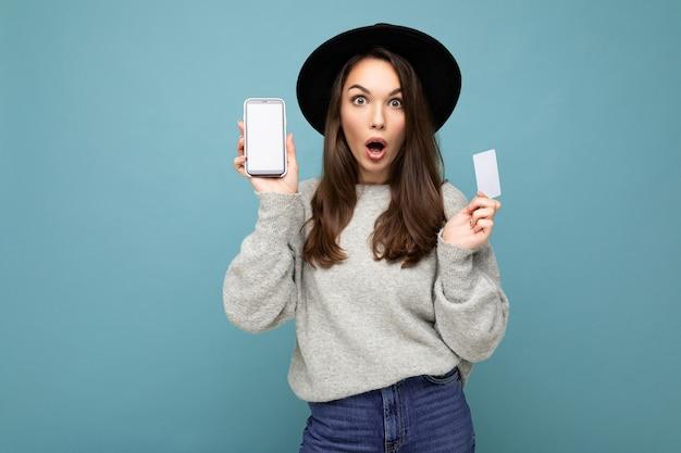 Attraktive schockierte junge brünette frau mit schwarzem hut und grauem pullover einzeln auf blauem hintergrund mit kreditkarte und handy mit leerem display für modell mit blick in die kamera.
