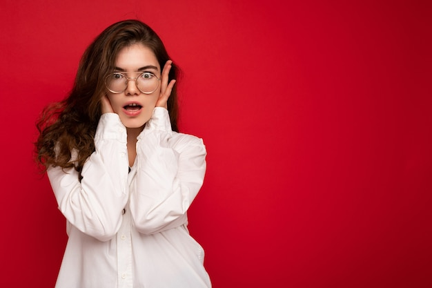 Attraktive schockierte überraschte überraschte junge lockige brünette frau, die weißes hemd und optisches trägt