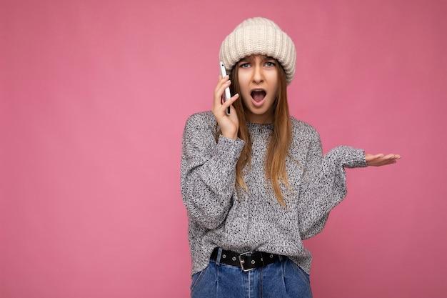 Attraktive schockierte verblüffte junge blonde frau, die lässigen grauen pullover und beigen hut isoliert trägt