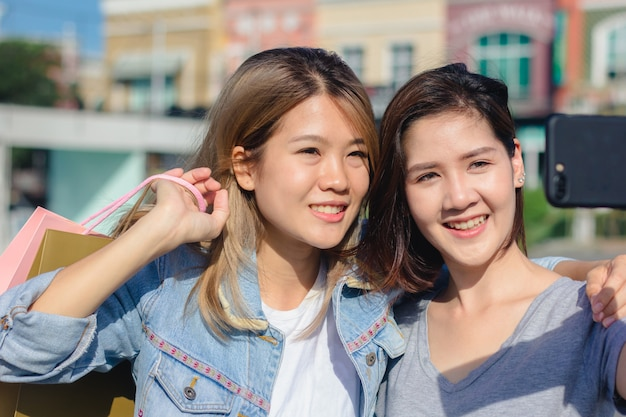 Attraktive schöne asiatische frau, die einen smartphone beim einkauf in der stadt verwendet