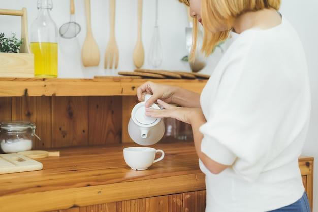 Attraktive schöne asiatische frau, die warmen kaffee in der küche an ihrem haus genießt