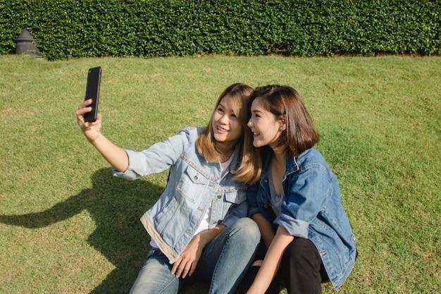 Attraktive schöne asiatische freundfrauen, die einen smartphone verwenden