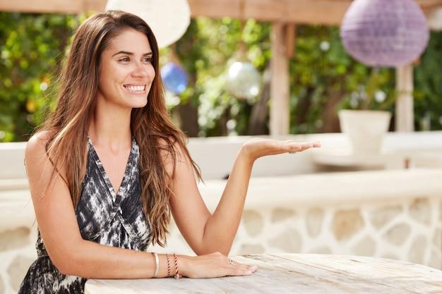 Attraktive schöne brünette frau mit langen haaren, entzücktem blick, hält die hand hoch, sitzt im terrassencafé, verbringt freizeit oder sommerferien im tropischen land.