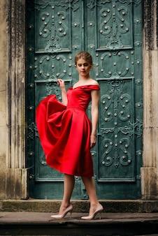 Attraktive schöne frau in einem roten kleid warf sie hoch