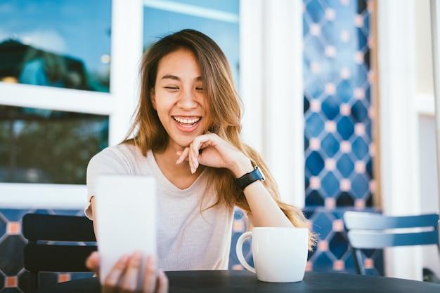 Attraktive schöne glückliche junge asiatin, die ein selfie unter verwendung eines intelligenten telefons am café nimmt