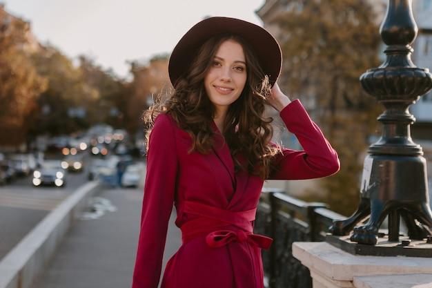 Attraktive schöne stilvolle frau im lila anzug, der in der stadtstraße geht, frühlingssommer-herbstsaison-modetrend, der hut trägt, geldbeutel hält
