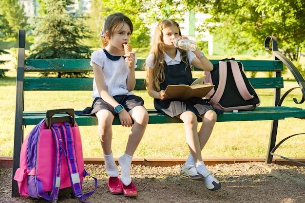 Attraktive schulmädchen der kleinen freundinnen mit rucksäcken