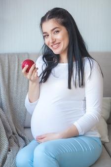 Attraktive schwangere frau mit apfel. erwartung der frau, die gesundes lebensmittel hält. dame, die einen roten apfel isst. richtige ernährung für die schwangerschaft.