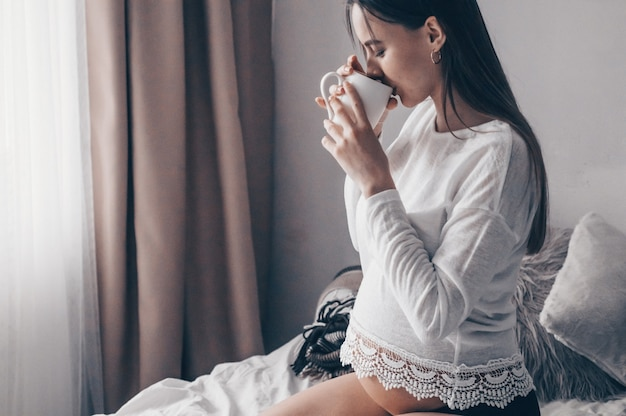 Attraktive schwangere frau trinkt tee auf dem bett. tee trinken, der durch ein fenster zu hause schaut. letzte monate der schwangerschaft.