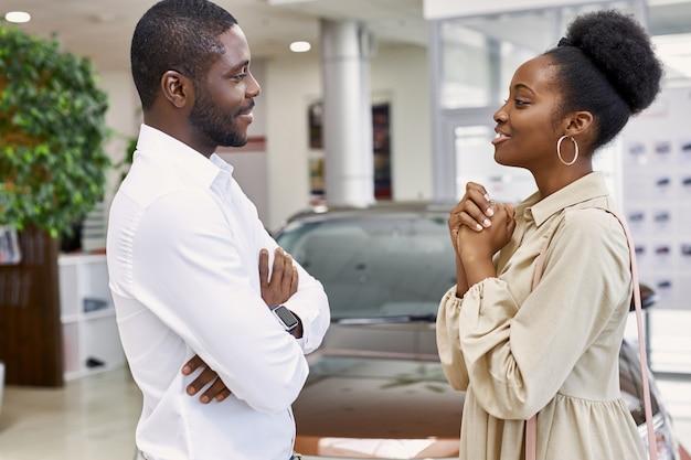 Attraktive schwarze dame bittet ihren mann, ein auto zu kaufen