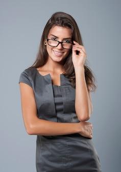 Attraktive sekretärin posiert mit ihrer brille
