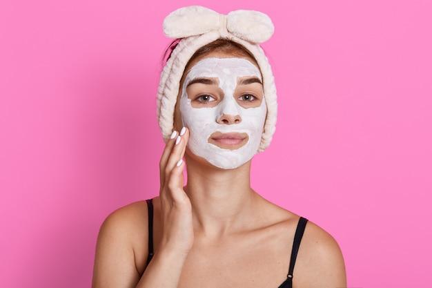 Attraktive selbstbewusste frau mit kosmetischer gesichtsmaske im gesicht hat schönheitsbehandlung, die gegen rosa wand aufwirft.