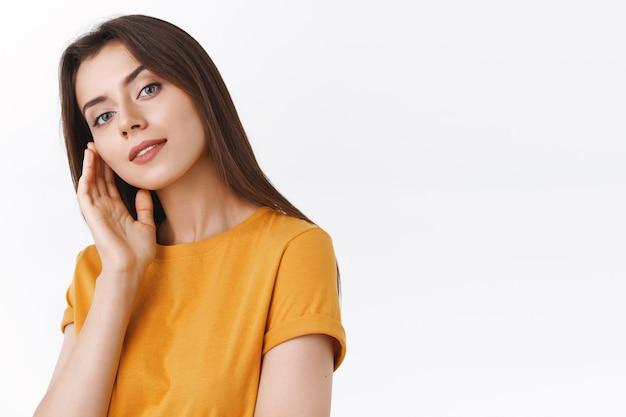 Attraktive, selbstbewusste, glamouröse brünette frau in gelbem t-shirt, die ein perfektes gesicht ohne makel berührt, den leicht geneigten kopf leicht geöffneter mund macht einen koketten, sinnlichen ausdruck, lächelnder weißer hintergrund