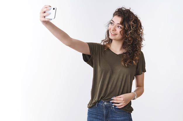 Attraktive, selbstbewusste, lockere bloggerin, die ein selfie macht, möchte ein neues bild posten, einen persönlichen blog, den arm ausstrecken, der das smartphone hält, das in der nähe des kühlen hintergrunds posiert, lächelndes telefondisplay