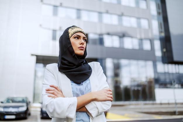 Attraktive selbstbewusste muslimische geschäftsfrau, die mit verschränkten armen vor ihrer firma steht.