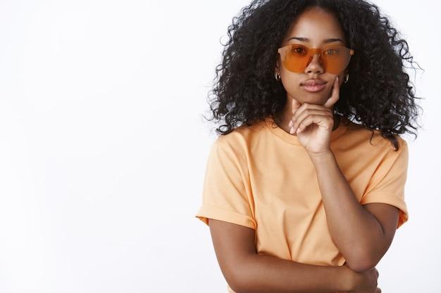 Attraktive selbstbewusste, stilvolle, modische dunkelhäutige moderne frau trägt eine sonnenbrille, ein orangefarbenes t-shirt, das das kinn berührt, sieht eine coole kamera aus, lächelt interessiert, fasziniert, steht weiße wand