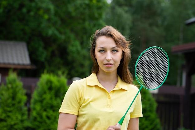 Attraktive sexy frau, die mit badmintonschläger im freien steht. sportbrünette auf grüner natur. aktive outdoor-sportspiele. training im freien