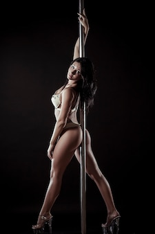 Attraktive sexy frau pole tänzerin vor grauem hintergrund