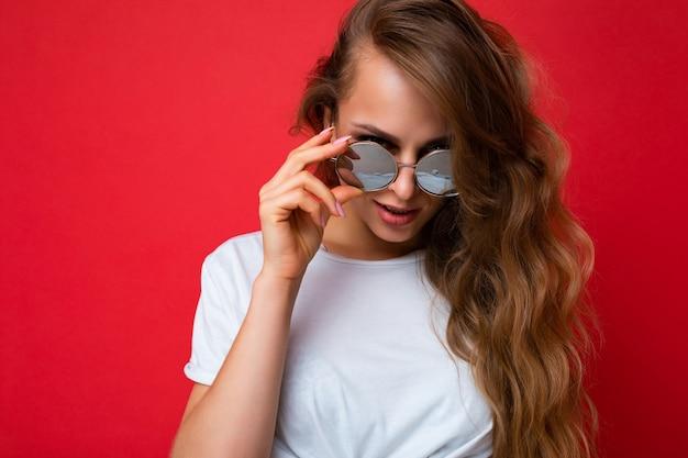 Attraktive sexy junge blonde frau, die alltägliche stilvolle kleidung und moderne sonnenbrillen trägt, die auf einer bunten hintergrundwand mit blick in die kamera isoliert sind