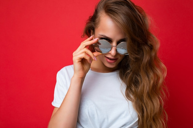 Attraktive sexy junge blonde frau, die alltägliche stilvolle kleidung und moderne sonnenbrillen trägt, isoliert