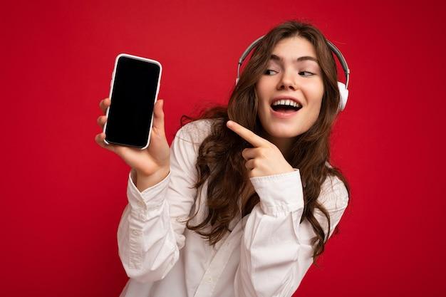Attraktive sexy positive junge brünette lockige frau mit weißem hemd isoliert auf rotem hintergrund