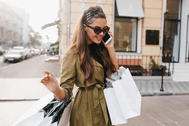Attraktive shopaholic frau mit gebräunter haut, die am telefon mit niedlichem lächeln spricht