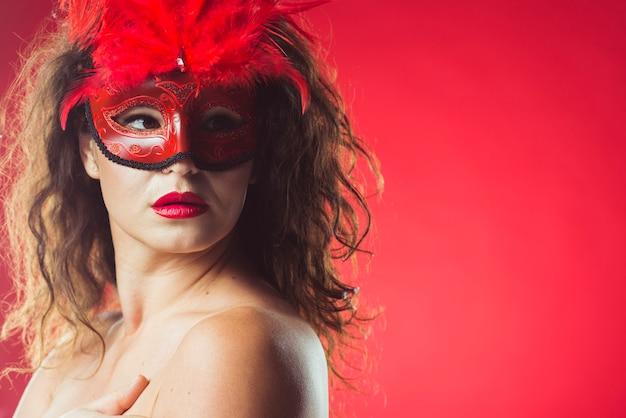 Attraktive sinnliche frau in der roten maske