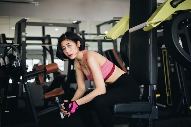Attraktive sitzfrau, die nach training in der turnhalleneignung sich entspannt