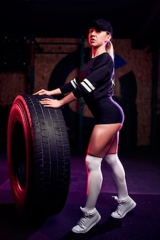 Attraktive sitzmittelalter-sportlerin, die mit einem enormen reifen in der turnhalle aufwirft. fit frau mit großen reifen