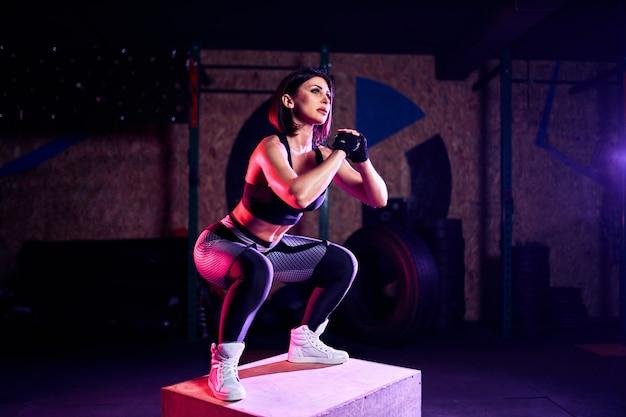 Attraktive sitzmittelalterfrau, die den kasten springt an einer kreuzsitzart tut. sportlerin führt sprünge an der turnhalle durch