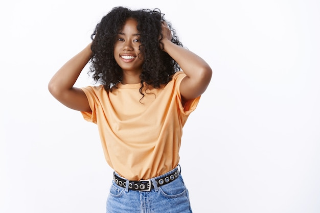 Attraktive sorglose junge afroamerikanerin, die ein trendiges orangefarbenes t-shirt trägt, das glücklich lächelt, afro-locken-haarschnitt berührt, begeistert, flauschiges haar fühlt, weiße wand steht
