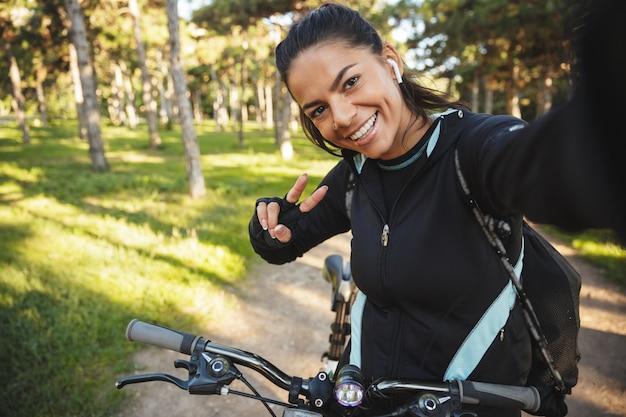 Attraktive sportlerin, die auf einem fahrrad im park fährt, musik mit drahtlosen kopfhörern hört und ein selfie macht
