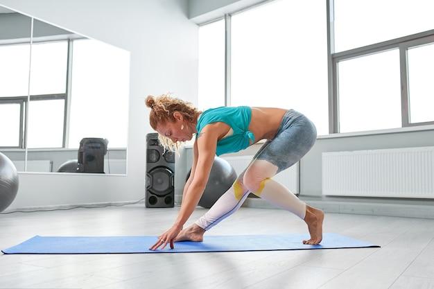 Attraktive sportlerin, die im modernen gaumenstudio übungen auf dem boden macht.