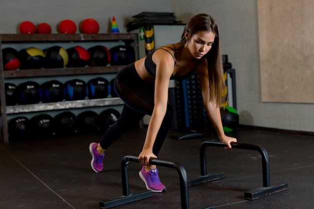 Attraktive sportlerin führt liegestütze aus, um die armmuskulatur im fitnessstudio inmitten von sportbällen zu stärken.