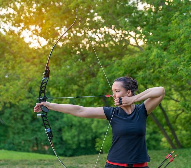 Attraktive sportlerin im bogenschießen, pfeile und bogen in aktion