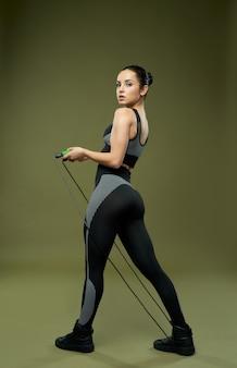 Attraktive sportliche dame in sportbekleidung, die springseil hält und die kamera mit ernstem ausdruck betrachtet. auf grünem hintergrund isoliert