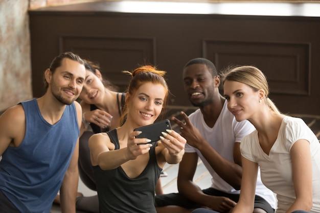 Attraktive sportliche frau, die das telefon nimmt gruppe selfie am tra hält