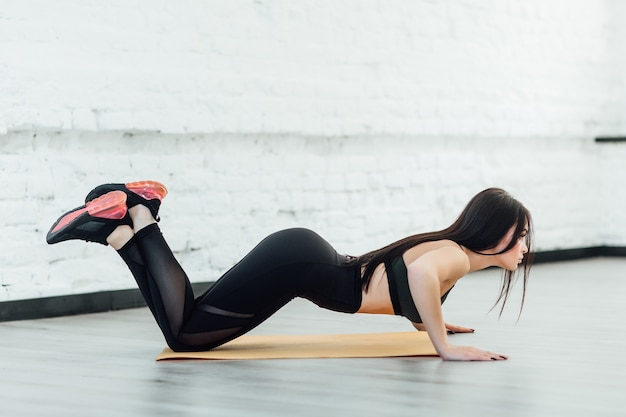 Attraktive sportliche frau, die übung auf yogamatte macht