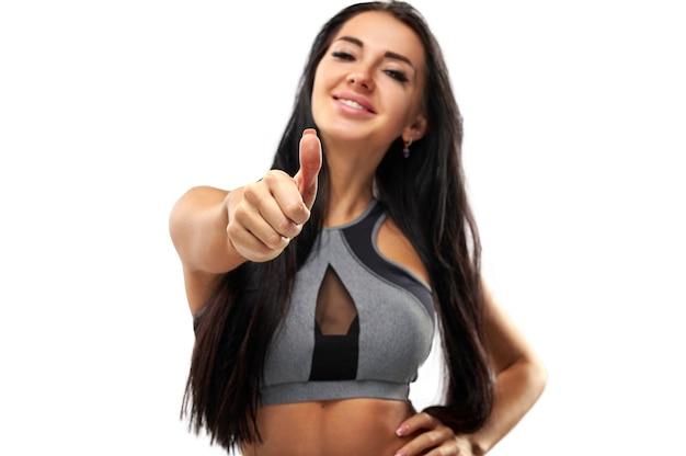 Attraktive sportliche frau in der sportbekleidung, die einen daumen nach oben zeigt und in die kamera lächelt. finger fokussieren