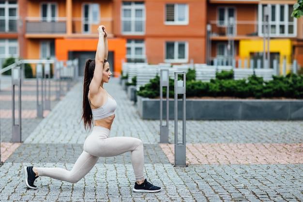 Attraktive sportliche frau in der stadt, nahe zu hause. junge perfekt geformte brünette macht kniebeugen.