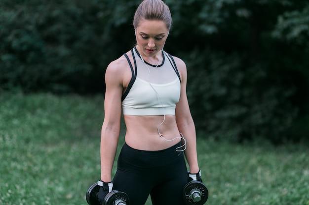 Attraktive starke frau in der sportkleidung hält dummköpfe in ihren armen, die draußen stehen