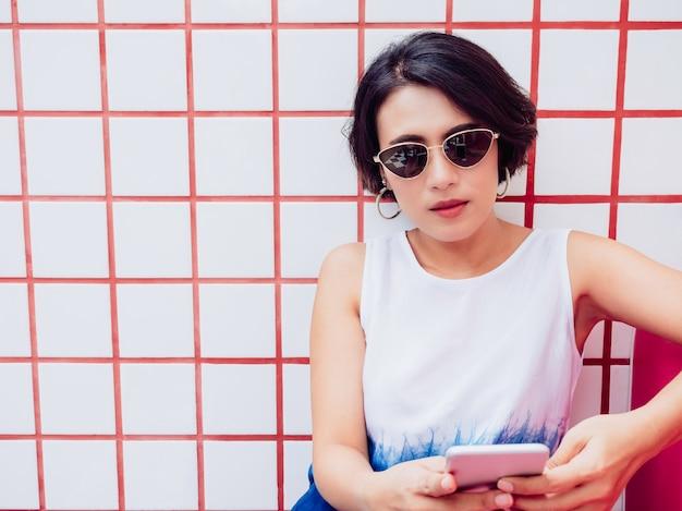 Attraktive stilvolle asiatische frau mit kurzem haar, die weißes hemd und sonnenbrille trägt, die auf rotem sitz sitzt und smartphone auf weißem und rotem fliesenwandhintergrund mit kopienraum verwendet.